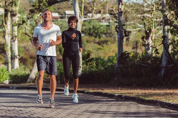 Homem e mulher correndo no parque.