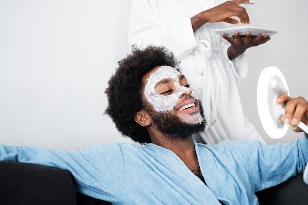 Homem e mulher cuidando do rosto em casa