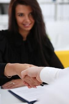 Homem e mulher cumprimentam-se com um aperto de mão no escritório.