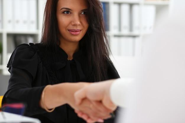 Homem e mulher cumprimentam-se com um aperto de mão no escritório