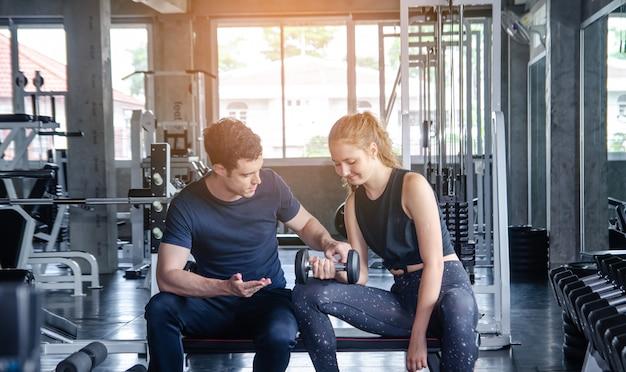 Homem e mulher da aptidão que dão-se uns cinco altos após a sessão de formação na ginástica.