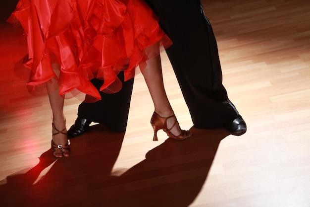 Homem e mulher dançando salsa em fundo escuro