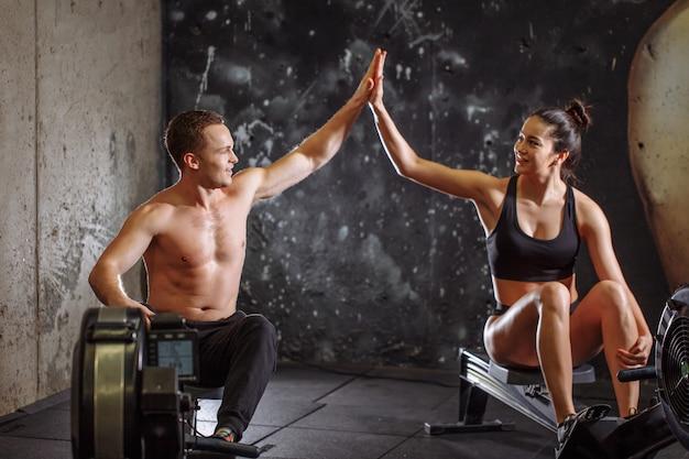 Homem e mulher dando mais cinco enquanto fazia exercícios com a máquina de remo