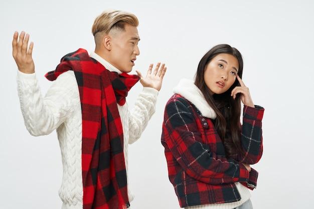 Homem e mulher de aparência asiática com cachecol e jaqueta xadrez