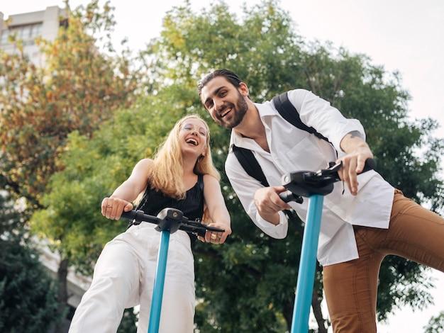 Homem e mulher de baixo ângulo usando scooters ao ar livre