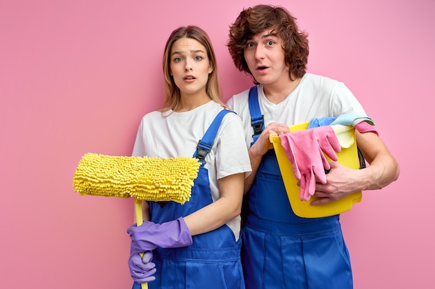 Homem e mulher de macacão e luvas de borracha olham para a câmera segurando ferramentas de limpeza isoladas sobre o fundo rosa do estúdio