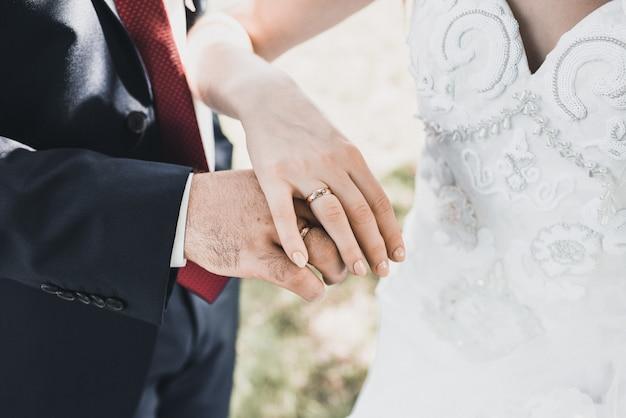 Homem e mulher de mãos dadas com os anéis de casamento da noiva e do noivo no fundo