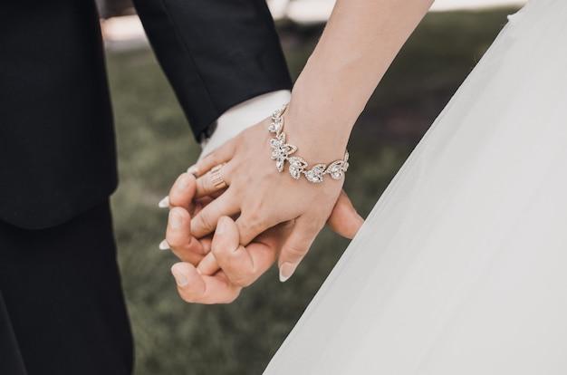 Homem e mulher de mãos dadas com os anéis de casamento dos noivos