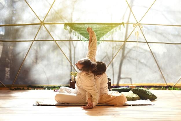 Homem e mulher de mãos dadas e apoiados um no outro, fazendo uma prática de ioga como um casal.