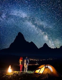 Homem e mulher de mãos dadas, em pé perto da fogueira