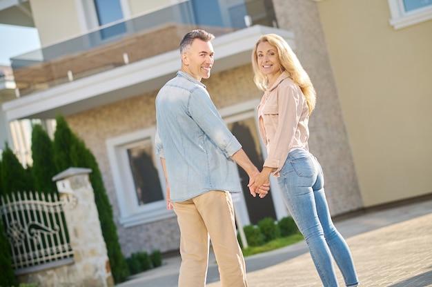 Homem e mulher de mãos dadas em pé, virados Foto Premium