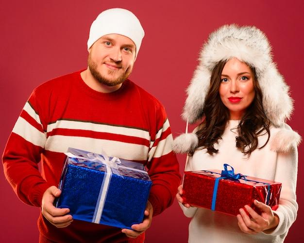 Homem e mulher de natal segurando presentes