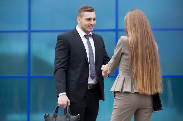 Homem e mulher de negócios apertando as mãos na rua