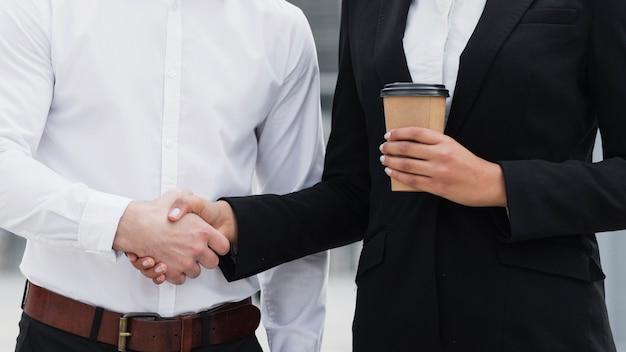 Homem e mulher de negócios, apertando as mãos
