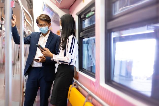 Homem e mulher de negócios asiáticos usando máscaras durante a pandemia de covid-19 enquanto viajam de transporte público