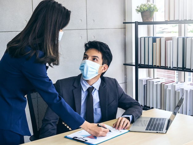 Homem e mulher de negócios asiáticos usando terno e máscaras protetoras olham para o gráfico do relatório