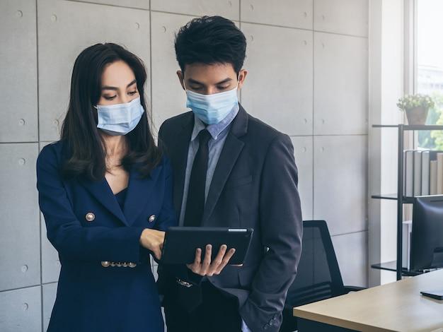 Homem e mulher de negócios asiáticos vestindo terno e máscaras protetoras usando tablet digital