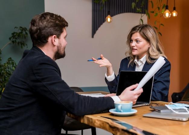 Homem e mulher de negócios falando sobre um projeto de trabalho