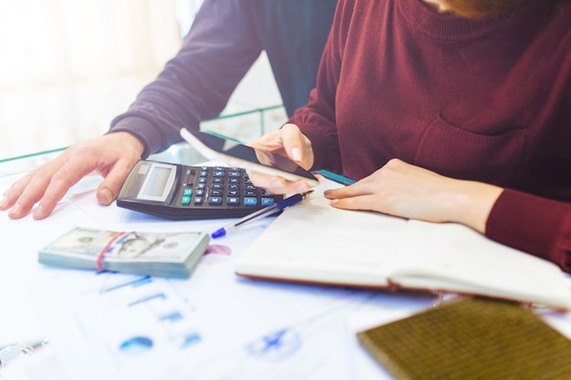 Homem e mulher de negócios trabalha em casa, trabalho remoto em casa, com laptop e bloco de notas, faz anotações no telefone, conta com uma calculadora