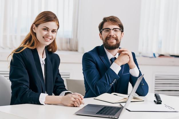 Homem e mulher de negócios trabalham juntos na frente da equipe de tecnologia do laptop