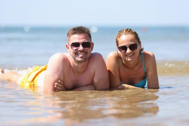 Homem e mulher de óculos escuros deitam-se lado a lado na água.