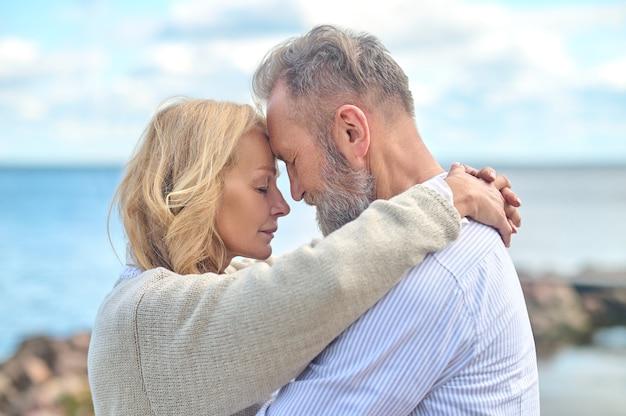 Homem e mulher de olhos fechados tocando rostos