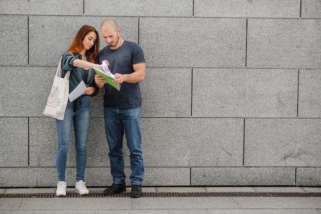 Homem e mulher de pé contra a parede cinza