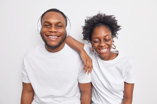 Homem e mulher de pele escura, alegre e despreocupada, se divertem e expressam emoções positivas.