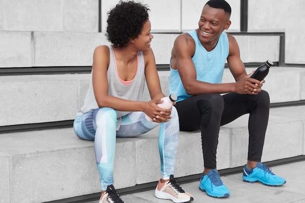 Homem e mulher de pele escura, alegre e motivada sentam-se na escada, olham positivamente um para o outro, seguram garrafas com água, usam roupas esportivas e tênis, discutem sobre competições esportivas.