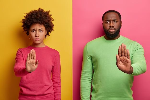 Homem e mulher de pele escura com aparência séria estendendo as palmas das mãos