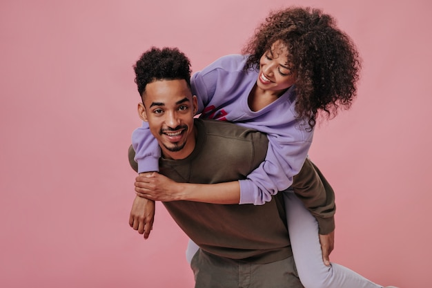 Homem e mulher de pele escura em moletons brincando na parede rosa