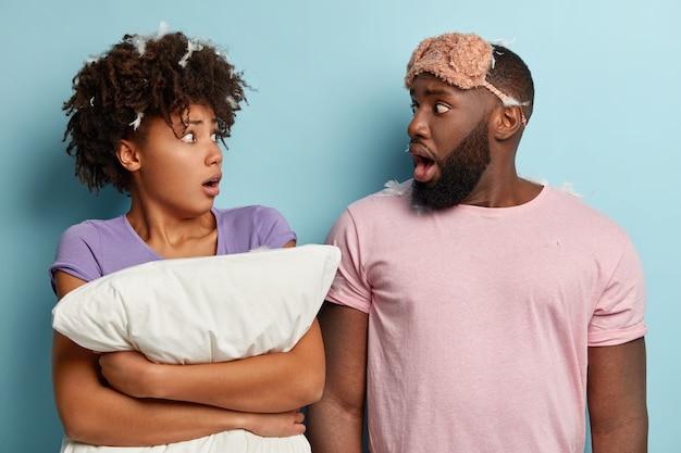 Homem e mulher de pele escura envergonhada e assustada se olham em choque, usam pijamas, máscara insatisfeita com o sono ruim, surpresos ao ouvir música alta dos vizinhos, isolados sobre a parede azul