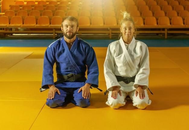 Homem e mulher de quimono azul e branco com faixa preta sentam-se no chão e meditam no pavilhão desportivo. artes marciais orientais, judô