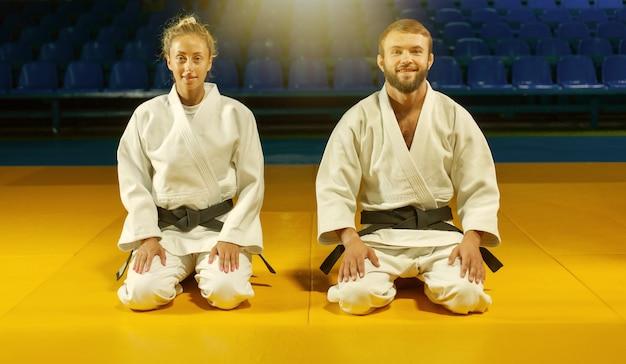 Homem e mulher de quimono branco com faixa preta sentam-se no chão e meditam no pavilhão desportivo. artes marciais orientais, judô