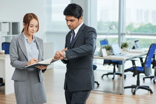 Homem e mulher de terno, olhando para o relógio de pulso