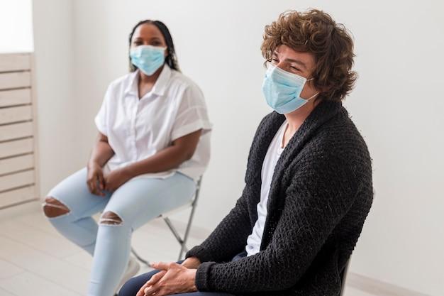 Homem e mulher de tiro médio com máscaras
