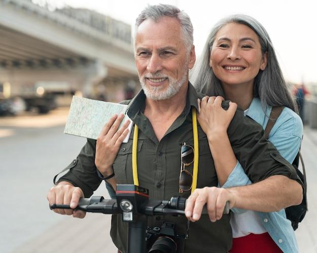 Homem e mulher de tiro médio com scooter