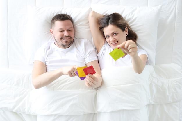 Homem e mulher deitados na cama com a visão superior dos preservativos