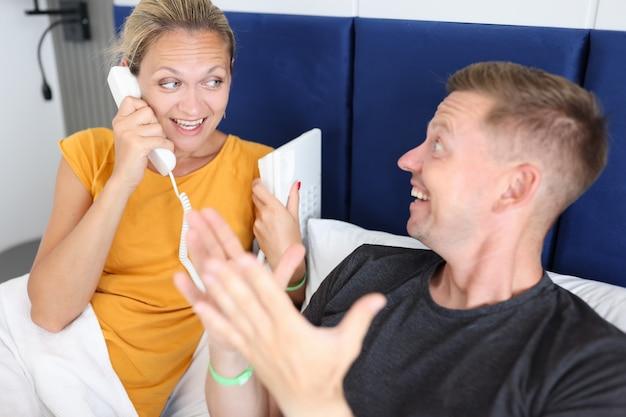 Homem e mulher deitados na cama falando ao telefone