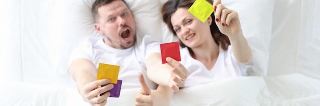 Homem e mulher deitados na cama segurando preservativos, vista superior, conceito de métodos anticoncepcionais