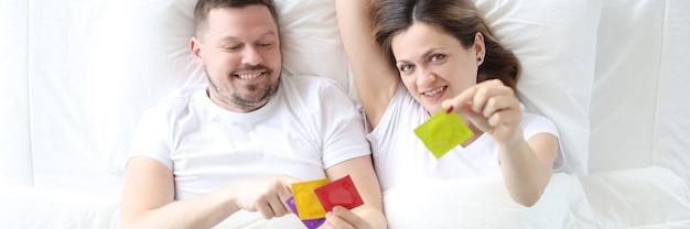 Homem e mulher deitados na cama segurando preservativos, vista superior, conceito de planejamento de gravidez