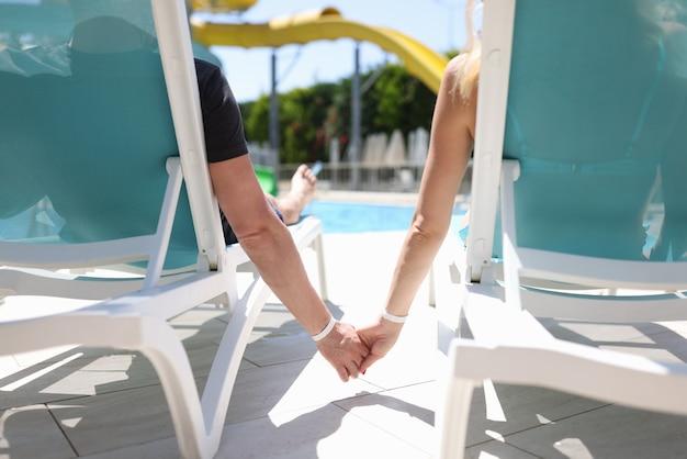 Homem e mulher deitados nas espreguiçadeiras perto da piscina e de mãos dadas, closeup
