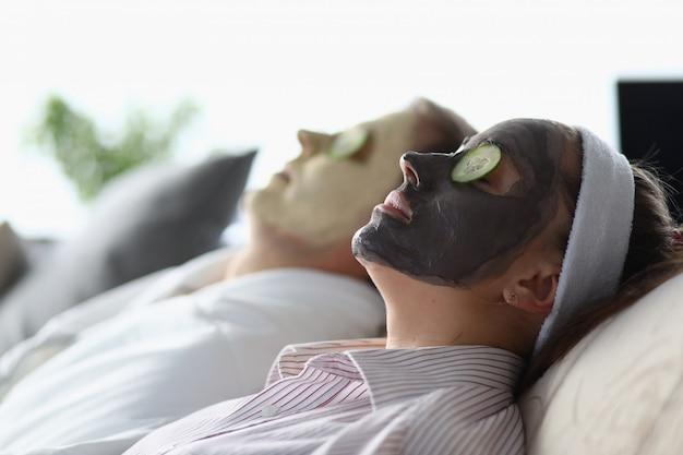 Homem e mulher deitar com máscara seus pepinos rostos