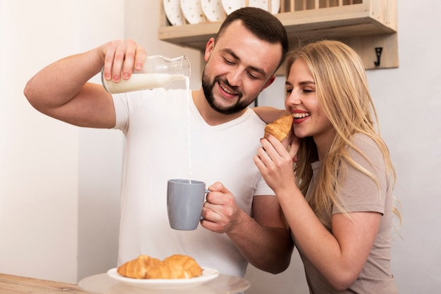Homem e mulher derramando leite e comendo croissants