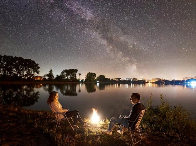 Homem e mulher descansando na praia sob o céu noturno