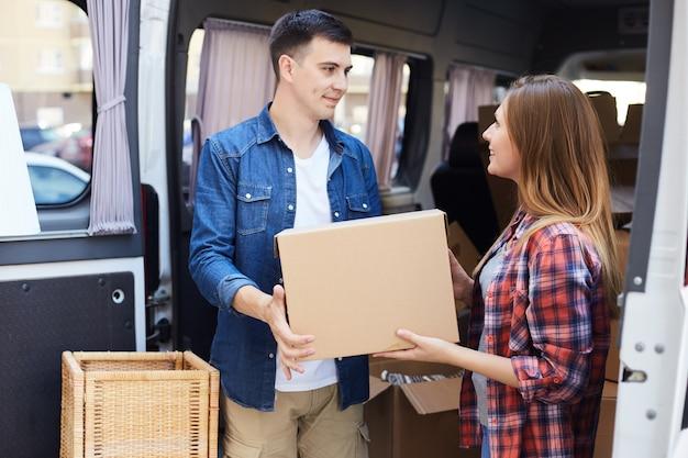 Homem e mulher, descarregando a van em movimento