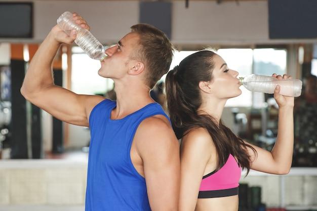 Homem e mulher desportivos bebendo água mineral costas com costas