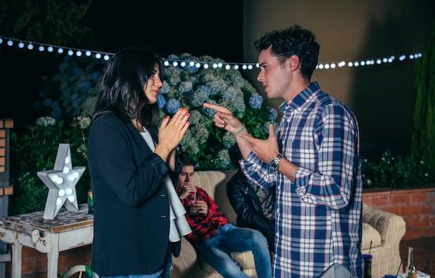 Homem e mulher discutindo em uma festa à noite ao ar livre com seus amigos. casal relacionamentos e conceito de problemas.