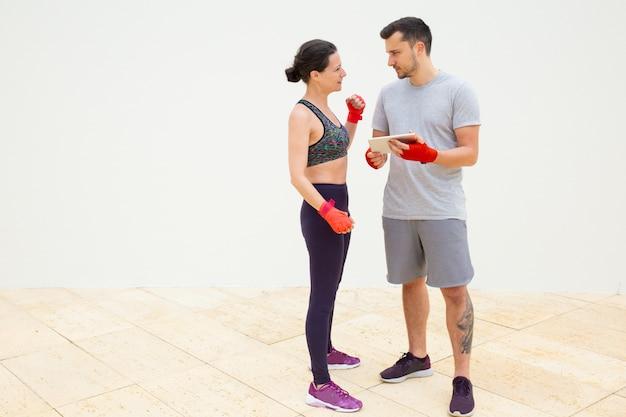 Homem e mulher discutindo o plano de treinamento com as mãos embrulhadas