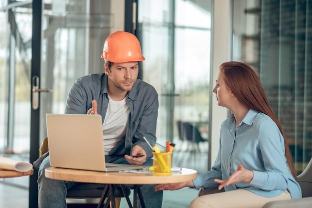 Homem e mulher discutindo plano de construção